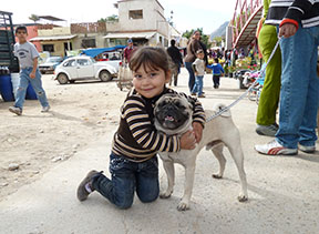 Child and pug at Las Tianguas, the Sunday market where hundreds of people from the countryside are bussed in to shop for food and goods.